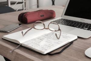 Tavolo di studio, con quaderno, occhiali, computer portatile e cellulare
